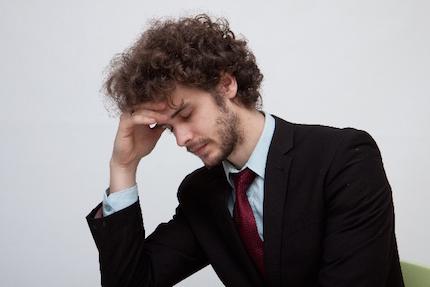 頭痛で苦しむ男性
